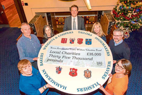 Trades Widows Fund Charity trustee Dan Smith, centre, with representatives from the various charities who are celebrating their cash windfall