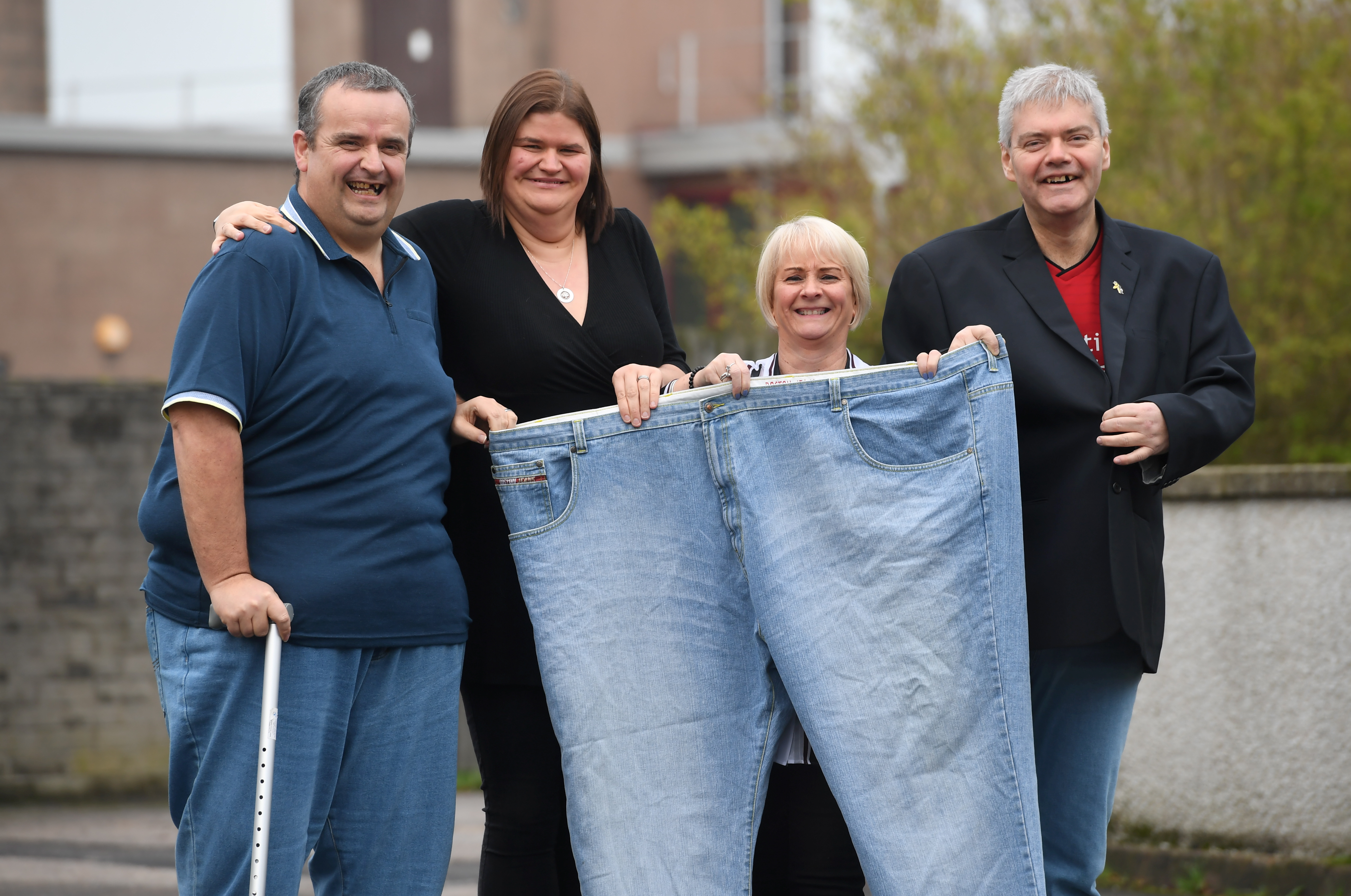 Showing off a pair of Kevin's  old jeans are friends, from left, Kevin Duncan, his wife Carrie Robertson-Duncan, Pam Brown and partner Jim Blagden
