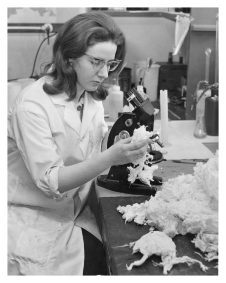 Miss Mary Boyne, a laboratory assistant, using a microscope to examine minute flaws in the paper, and looks at the processed rags, the raw material used in making the paper
