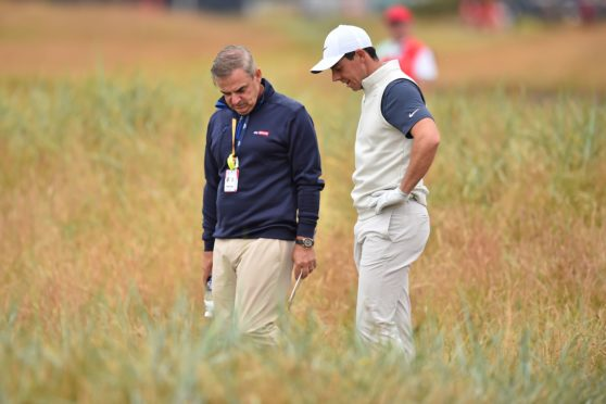 Northern Ireland's Rory McIlroy studies his ball in the rough with former Ryder Cup captain Paul McGinley during a practice round at The 147th Open golf Championship at Carnoustie, Scotland in July.