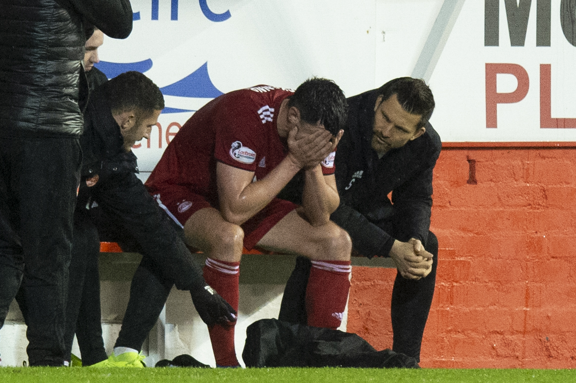 Scott McKenna looks dejected after being forced off with an injury.