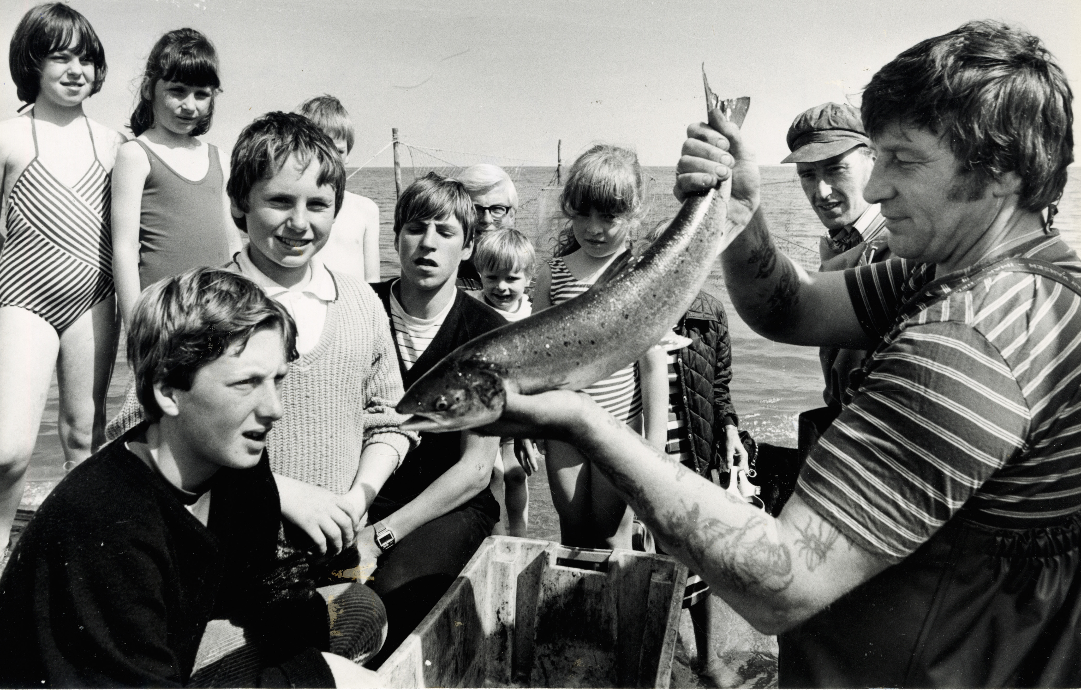 A silver salmon from the nets at Aberdeen Beach holds the attention of youngsters and adults alike as fishermen Tommy Thomson and Bob Nicholson show the fish to the holiday makers