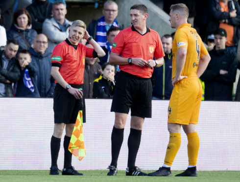 Assistant referee Calum Spence feels the back of his head as referee Craig Thomson and Livingston's Alan Lithgow look on.