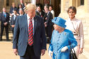 Queen Elizabeth II, US President Donald Trump and first lady Melania Trump walk in the Quadrangle during a ceremonial welcome at Windsor Castle, Windsor