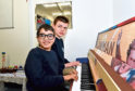 Two pupils at the school with the piano
