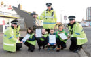Maja Urbanak, 10, Emily Guthrie, 10, Oli Dizcynski, 10 and Kascper Jurkiewicz, 10 with PC Greg Ferns,  Sergeant Malcolm Kinross and PC Ewan Forbes