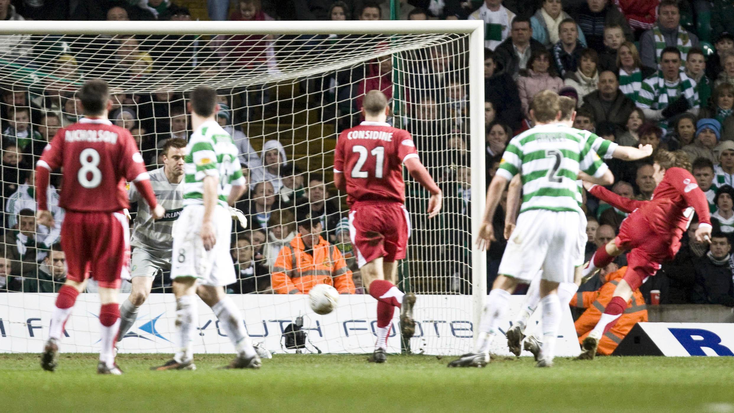 Aberdeen's Darren Mackie  thunders the ball under Celtic keeper Artur Boruc.