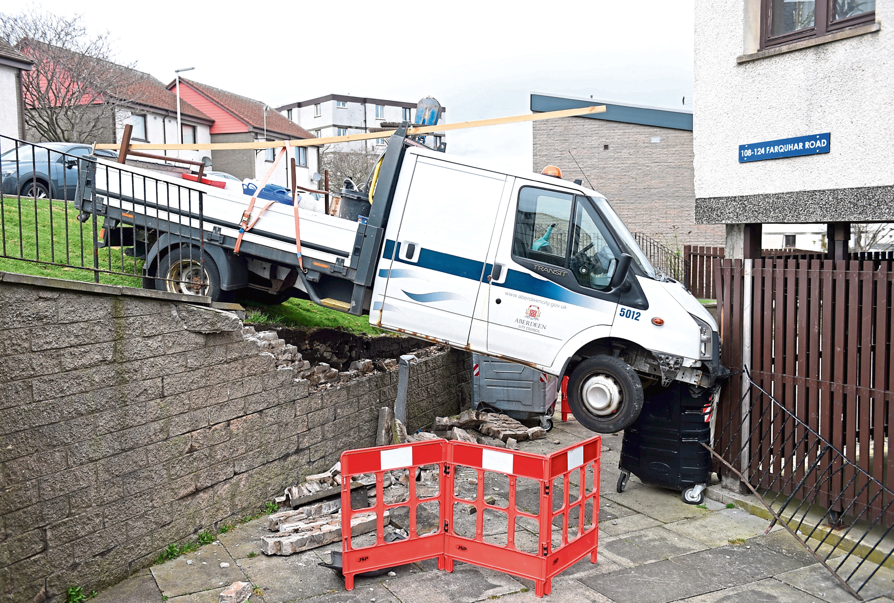 The council van smashed through a railing damaging a wall before coming to rest against a block of flats