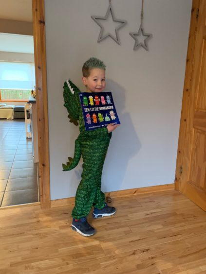 Rhys Winterbottom, 6, as a dinosaur with his favourite book Ten Little Dinosaurs