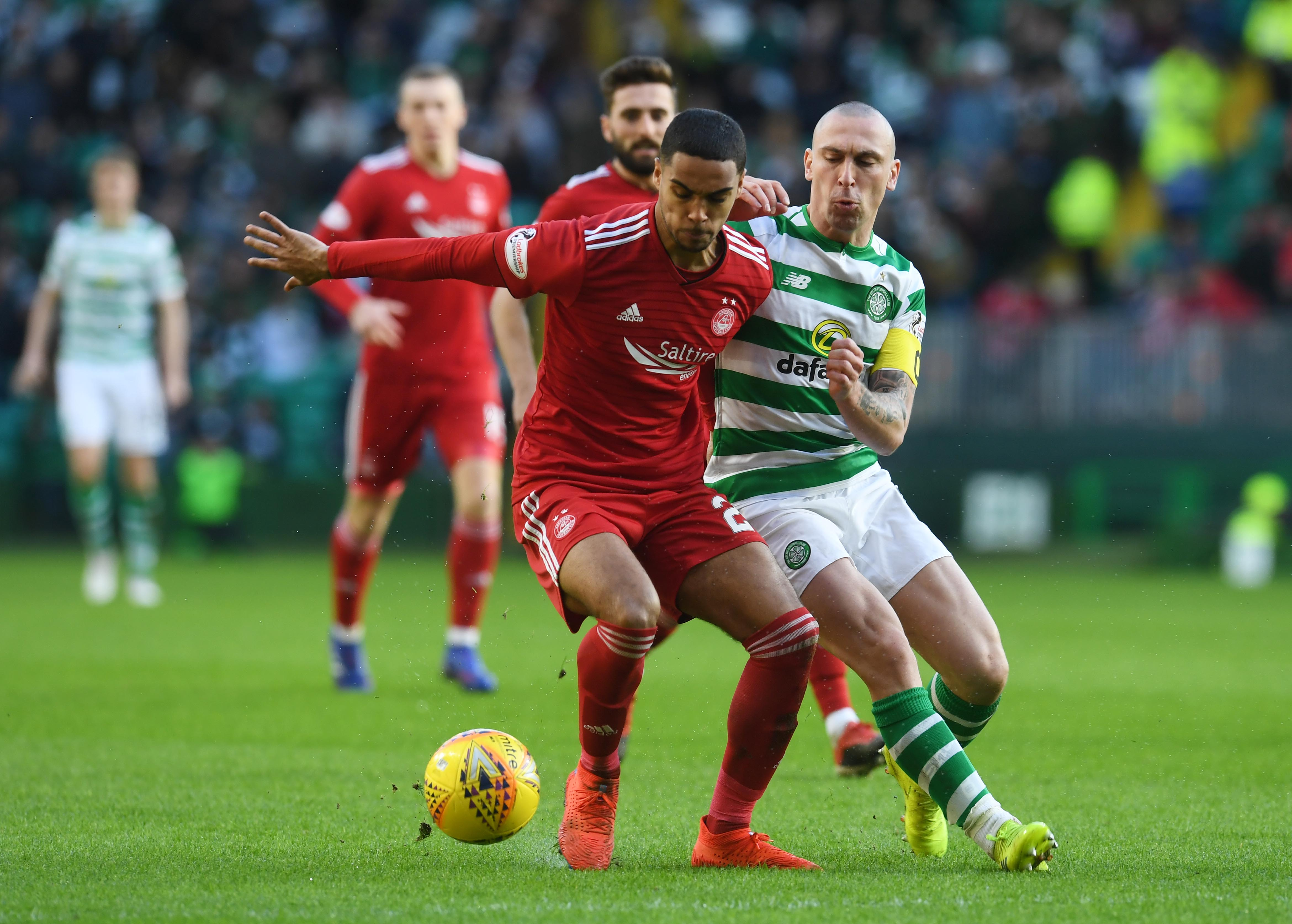 Aberdeen's Max Lowe (left) holds off Celtic's Scott Brown