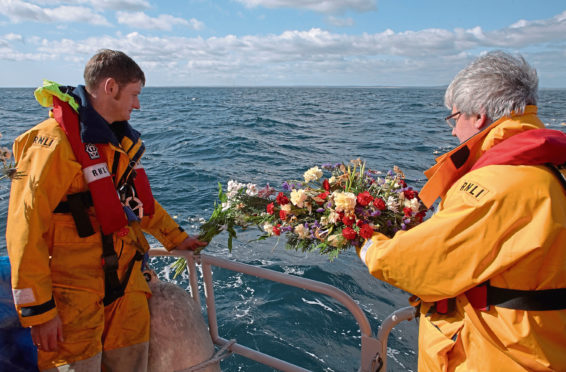 A member of the Fraserburgh Lifeboat crew, left, helps the Reverend Andrew Jolly lay wreaths