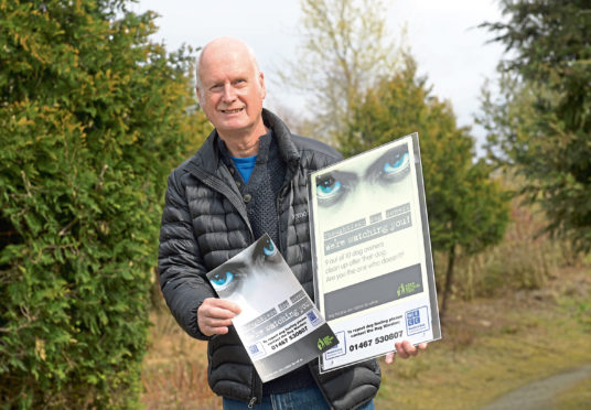 Ken Stewart with glow-in-the-dark posters for a campaign to tackle dog fouling