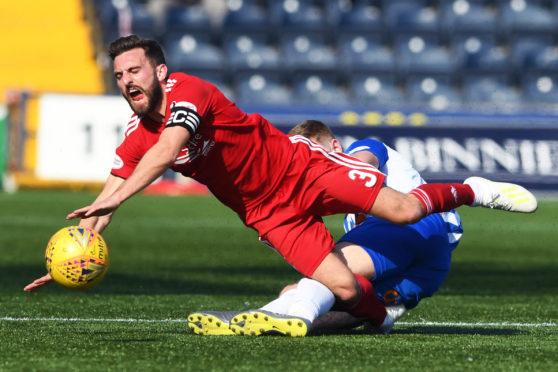 Kilmarnock's Stuart Findlay challenges Aberdeen's Graeme Shinnie and is sent off. Shinnie was left injured.
