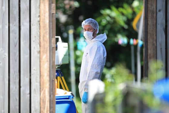 """A forensics officer at a property on Gregg House Road after two boys aged 13 and 14 died following a """"serious incident"""" in the Shiregreen area of Sheffield. Two people have been arrested. (Danny Lawson/PA)"""