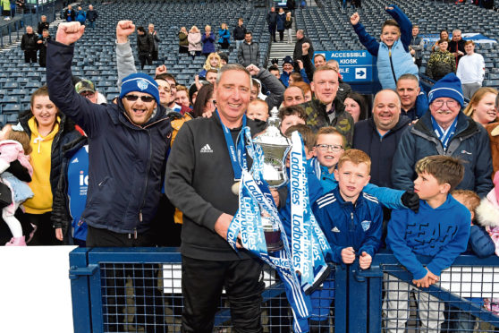 Peterhead manager Jim McInally celebrates with the League Two trophy and Peterhead's fans