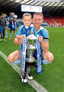 Peterhead captain Rory McAllister celebrates winning League Two with his son Noel
