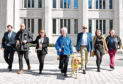 Cllr John Wheeler, Guide Niall Foles, Cllr Jackie Dunbar, Mary Rasmusen with her guide dog Vince, Cllr Ian Yuill, Guide Cate Vallis and Cllr Sandra MacDonald cross the road.
