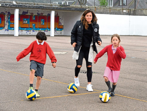 Rachel Corsie on a visit to  Ashley Road School, Aberdeen, prior to her departure for the Women's World Cup in France in June. In the picture Rachel warms up with Mohammed Selim and Ariana Chalmers.