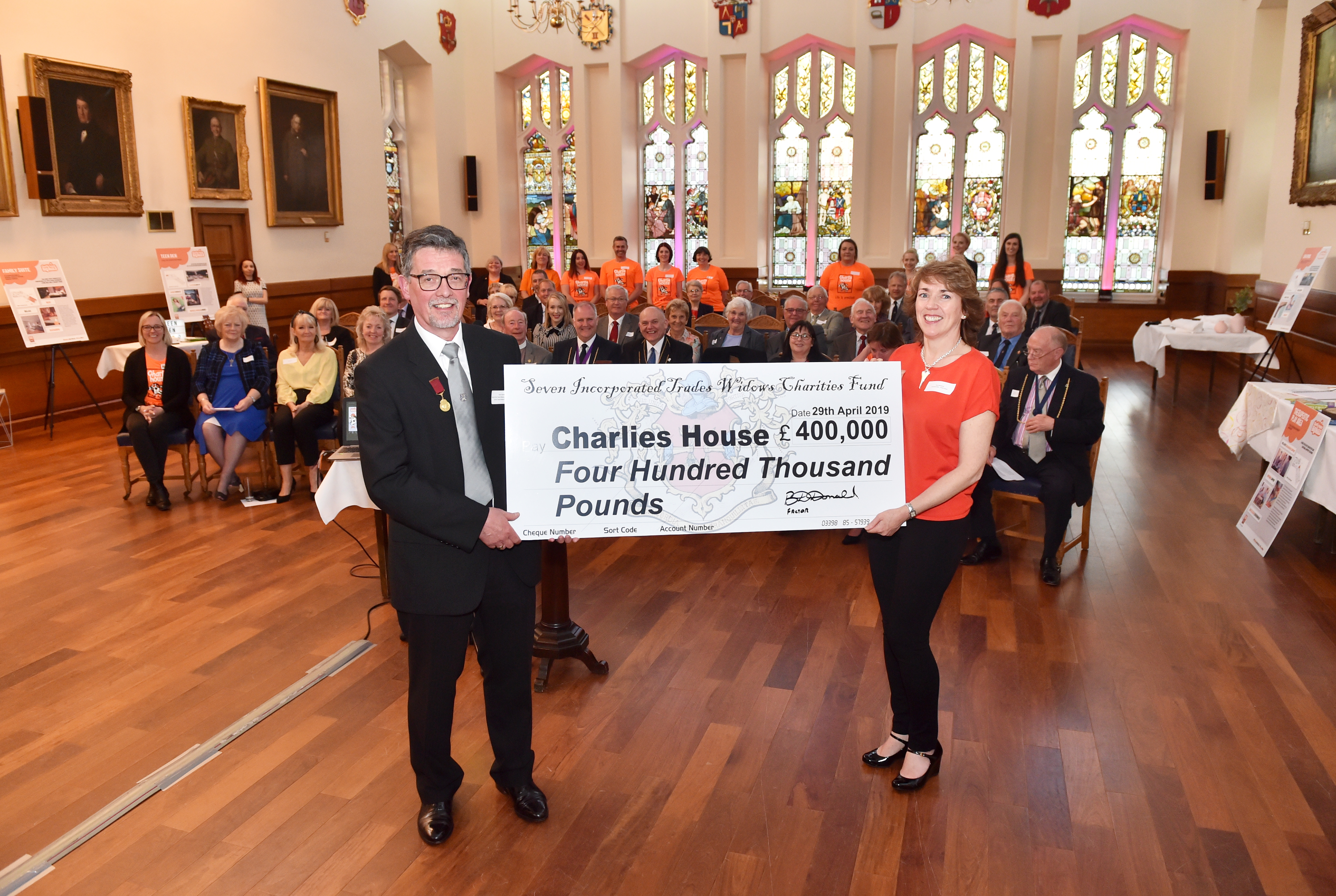 Seven Trades Factor Brian Donald and Tracy Johnstone of Charlie House with the donation which took the charity's total to over £2 million