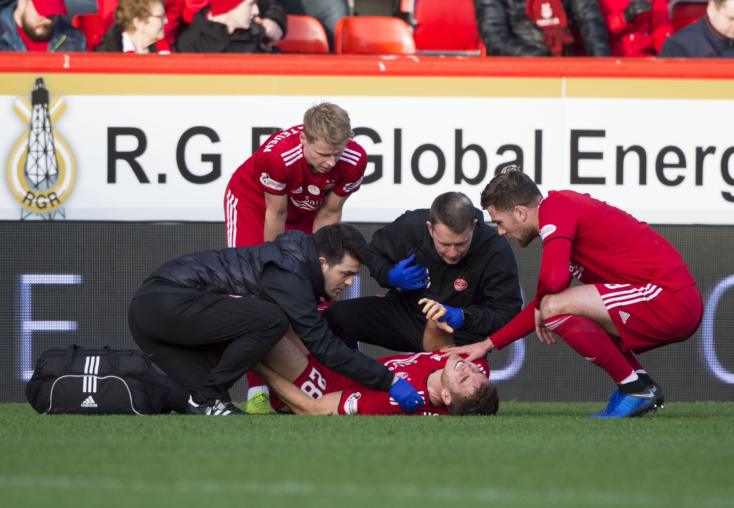 Aberdeen's Tommie Hoban is treated for his injury on the Pittodrie pitch.