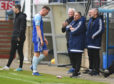 Peterhead's Rory McAllister is dejected as manager Jim McInally looks on.