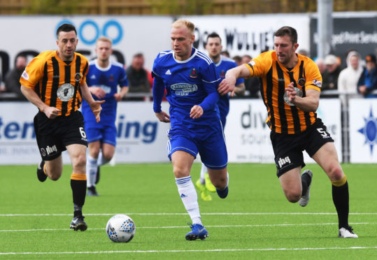 Cove Rangers' Jordon Brown, centre, drives away from Berwick Rangers' Declan O'Kane, right.