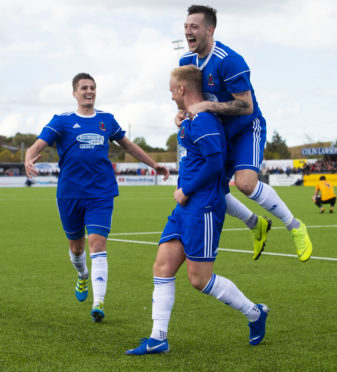 Jordon Brown (centre) celebrates with his teammates after Cove scored their third goal..