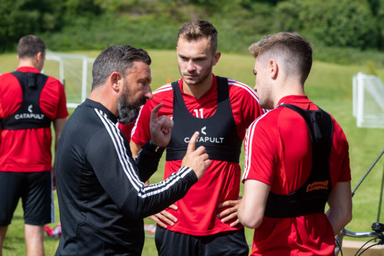 McInnes speaks with new signing Ryan Hedges, left.