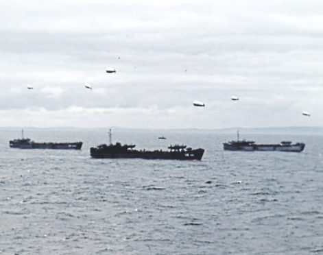 Ships and blimps sit off the coast of France on D-Day, June 6, 1944