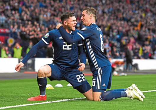 Scotland's Oliver Burke celebrates his late goal earlier this year with Kenny McLean, right.