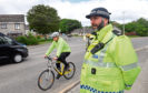 Sergeant Peter Henderson and PC Brian Pirie, cycling, on Denmore Road, Bridge of Don in an operation to urge drivers to give cyclists space when passing