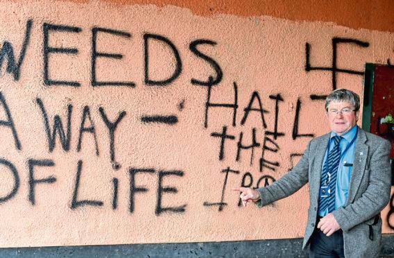 Councillor Iain Taylor at the graffitied wall