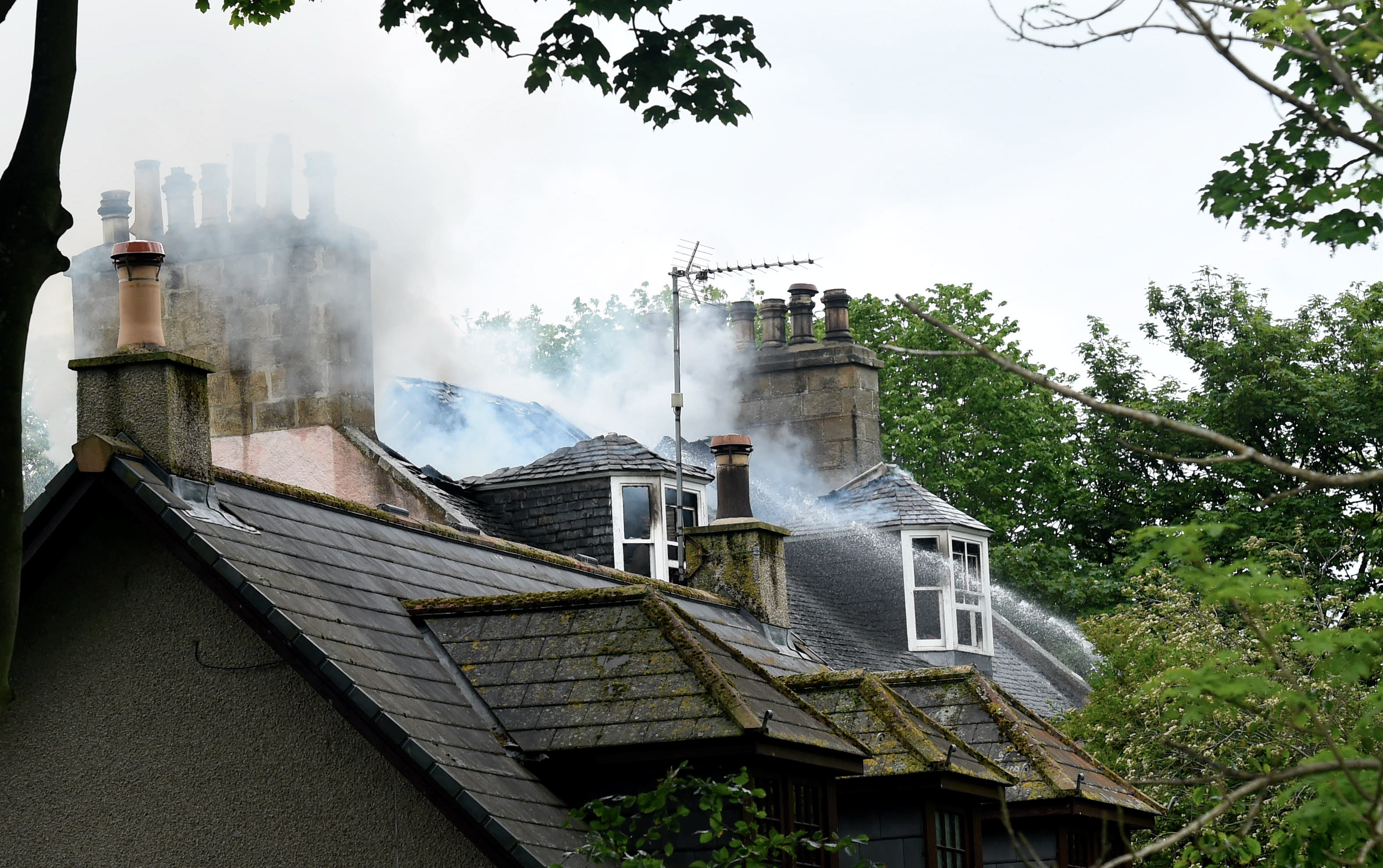 Fire crews were forced to leave the building after the blaze spread to the roof