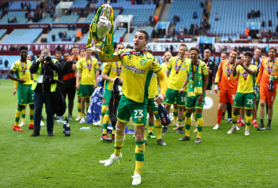Kenny McLean of Norwich City lifts the championship trophy in celebration after the Sky Bet Championship match between Aston Villa and Norwich City at Villa Park on May 5.