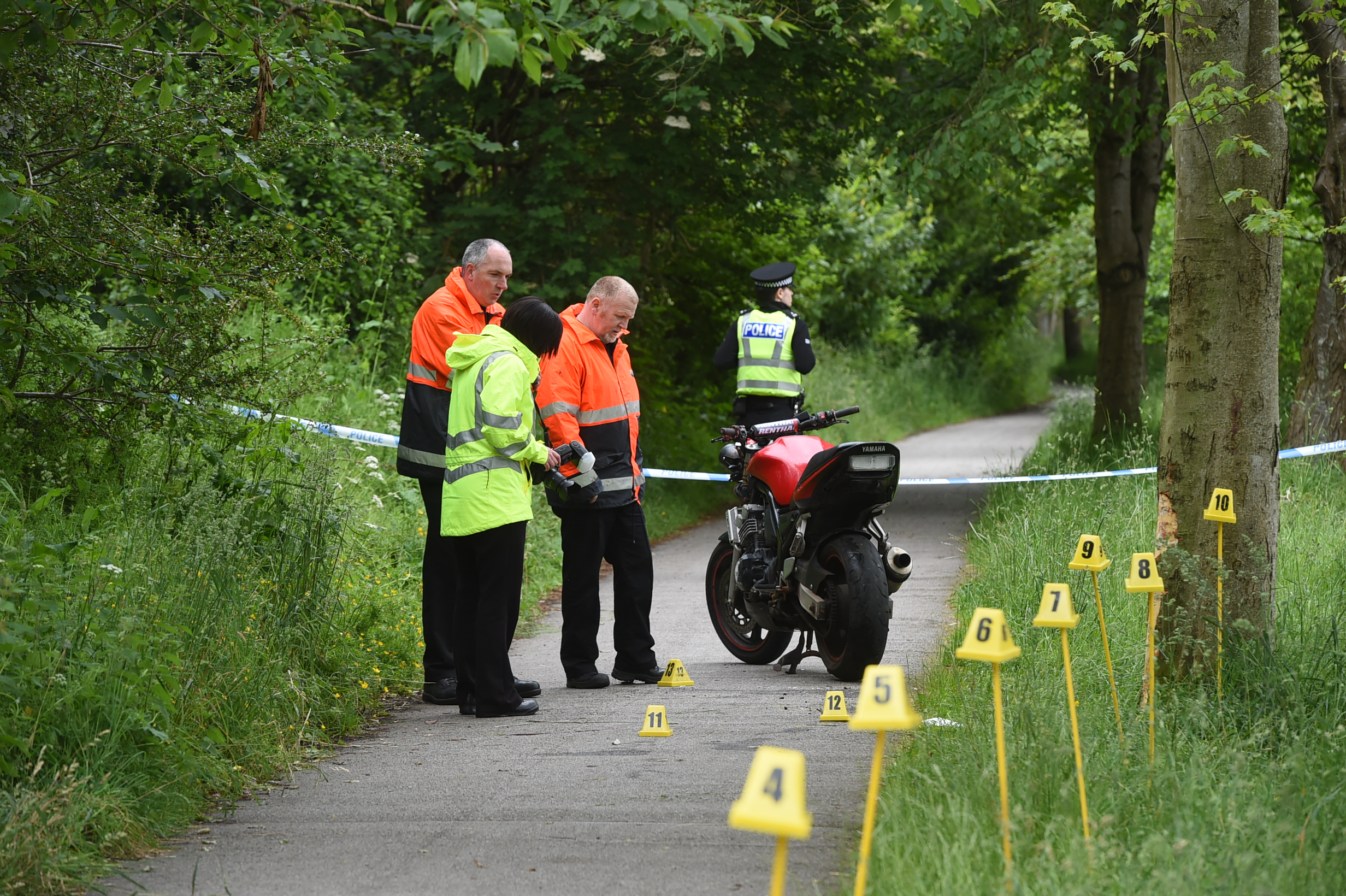 Investigating officers at the scene of a motorbike crash on the Deeside Railway Line