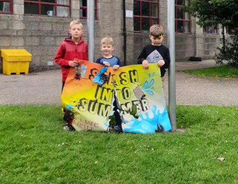 Strichen School youngsters, from left, Nathanial Carlsson-Bell, 8, Ollie Taylor, 5, and Finn Taylor, 7, with the vandalised sign