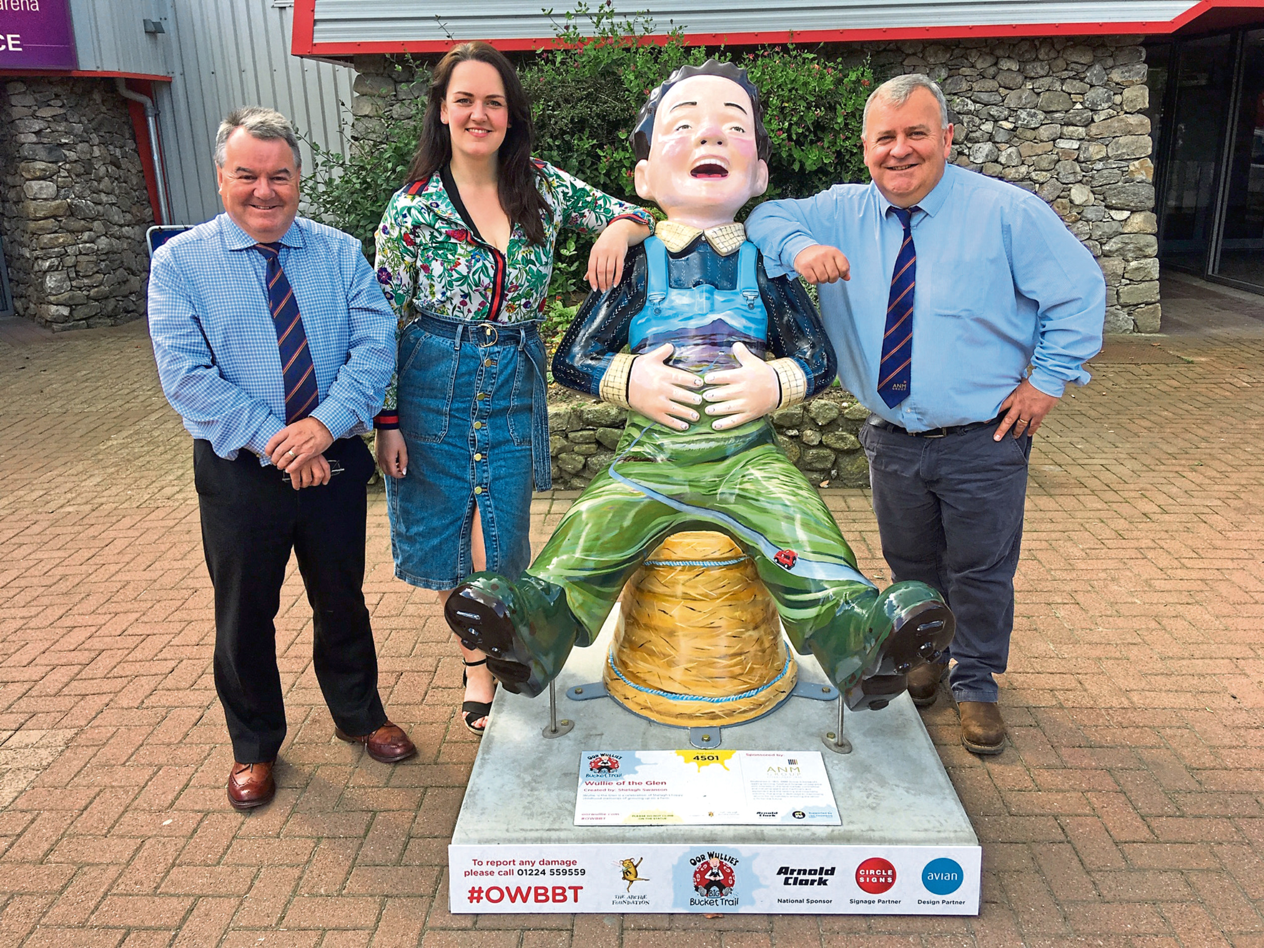 Auctioneers Alan Hutcheon and Colin Slessor with Shelagh Swanson, the artist of 'Wullie of the Glen' located at the front entrance of Thainstone Centre