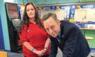 Liam Kerr MSP signs the pledge at the Portlethen Coral betting shop, watched by shop assistant Laurie