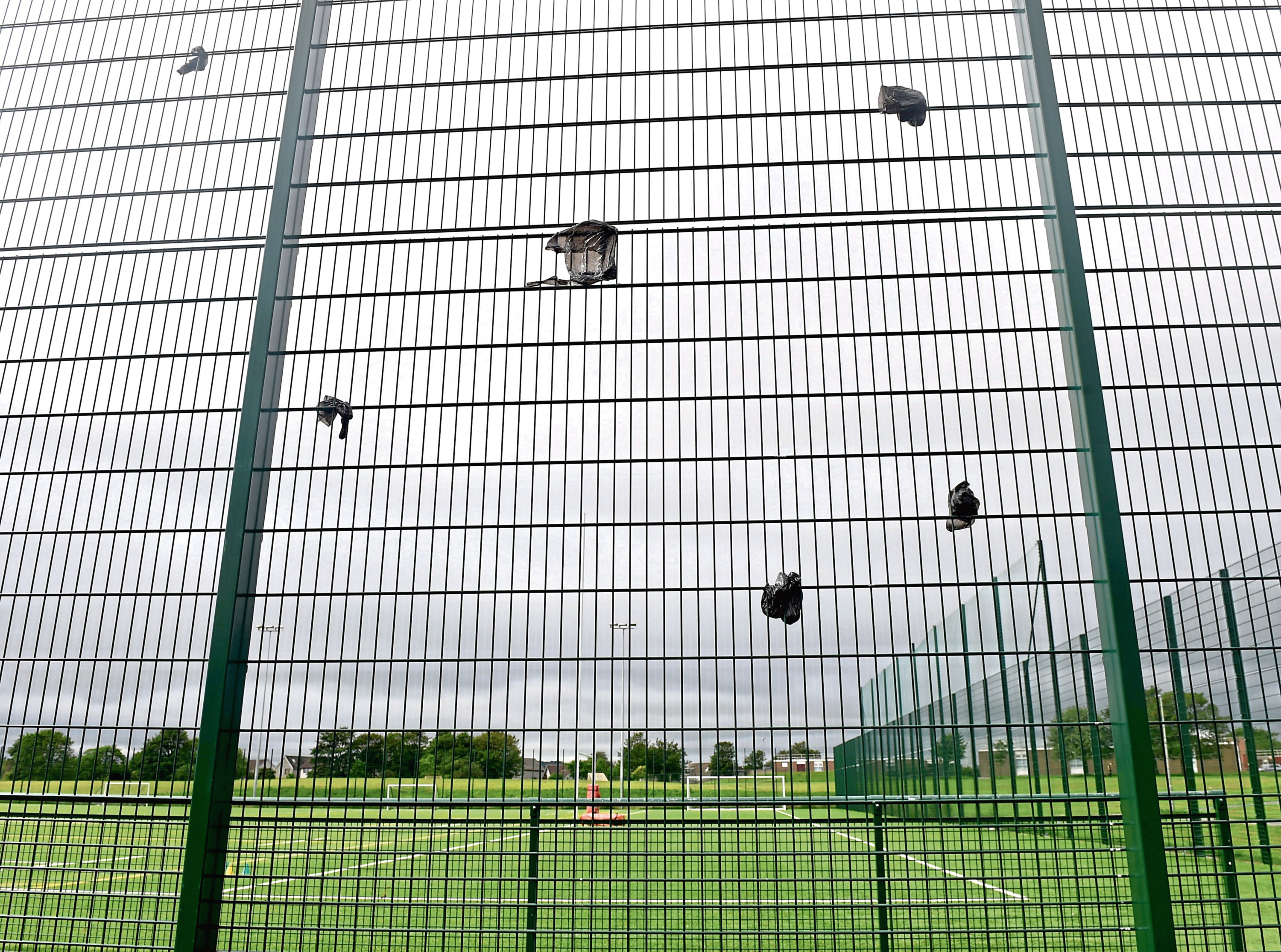 The waste bags have been left strewn across metal railings around the grounds at Dyce Academy