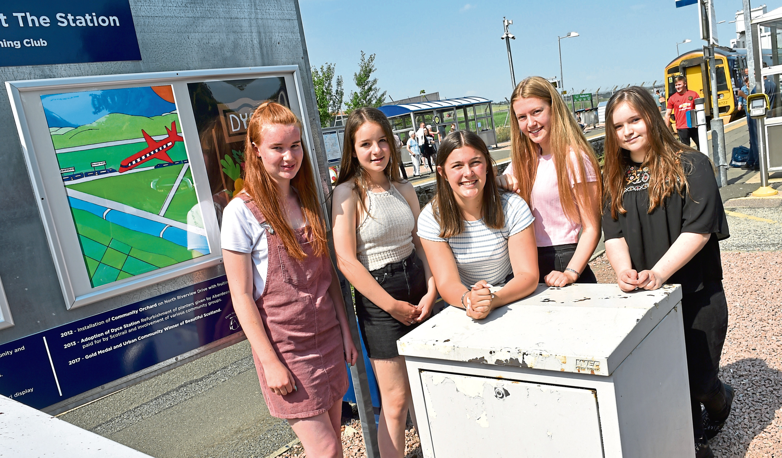 Kristi Mason, Leah Danraj, Kayla Spence, Hazel Emslie and Anna Coleman at Dyce station with the posters
