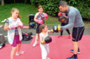 Boxer Lee McAllister, who has announced his latest title fight, and the children coached by Lee who are exhibiting their skills at a family fun day at Brig O' Don restaurant in Aberdeen Picture by Jim Irvine