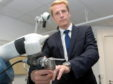 Consultant orthopaedic surgeon Martin Mitchell with the robotic arm