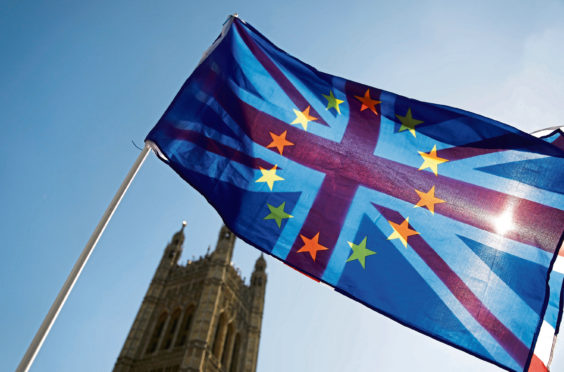 Brexit flag An activist waves a combination of the Union and the EU flags near the Houses of Parliament in central London on April 10, 2019. - The EU's chief Brexit negotiator said Tuesday that the length of any delay to the divorce that the bloc may grant Britain will depend on what plan Prime Minister Theresa May brings to a crunch summit. (Photo by Tolga AKMEN / AFP)        (Photo credit should read TOLGA AKMEN/AFP/Getty Images)