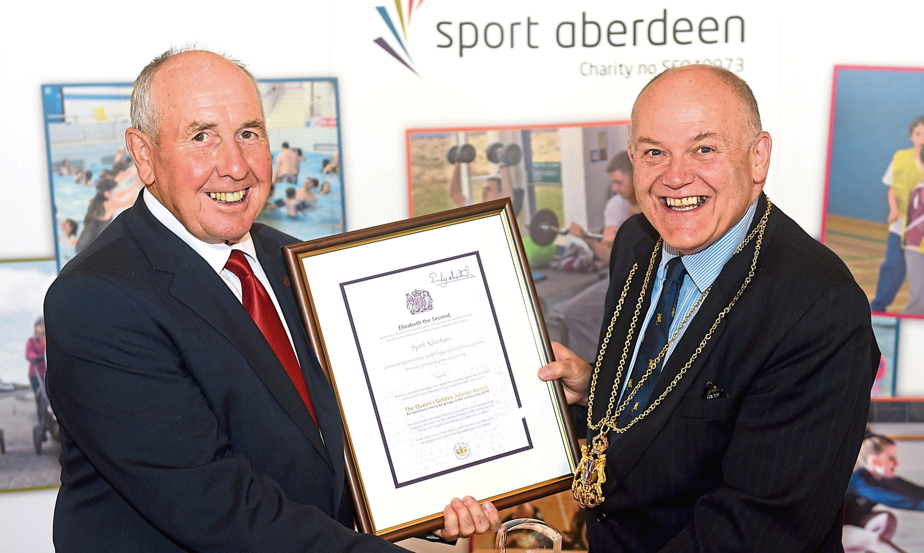Colin G Taylor being presented the Queen's Award for Voluntary Service by Councillor Barney Crockett