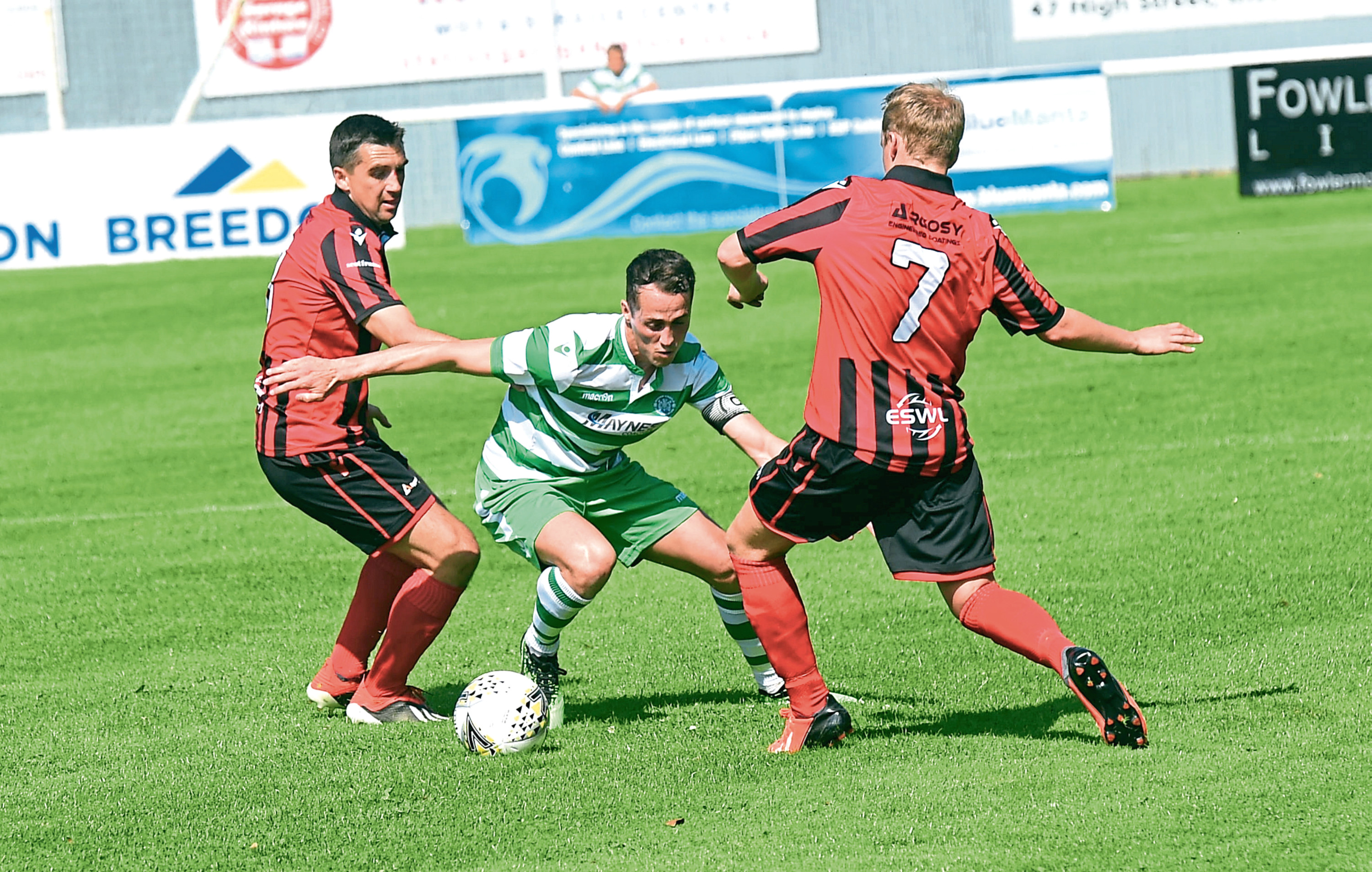 Loco's Neil Mclean and Jamie Michie and Buckie's Kevin Fraser.