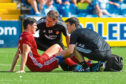 Aberdeen's Scott McKenna is forced off with a hamstring injury.