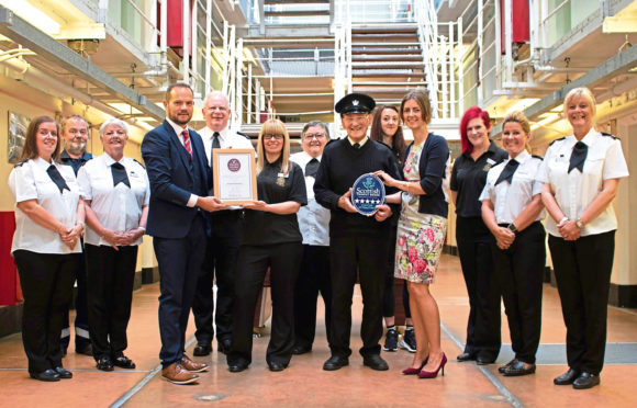Peterhead Prison Museum team with Den McFarlane (VisitScotland Industry Relationship Manager) and Jo Robinson (VisitScotland Regional Director) presenting the Taste Our Best and Five Star awards respectively. Handout Visit Scotland.