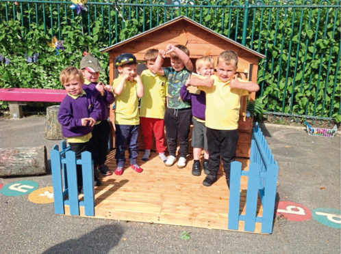 Some of the children of Braehead Nursery with the playhouse that was built for them by the Bridge of Don and District Men's Shed group.