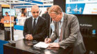 Restrata stand at OE, as well as a pic of CEO Botan Osman and one of him signing the deal with Serica Energy CEO Mitch Flegg.