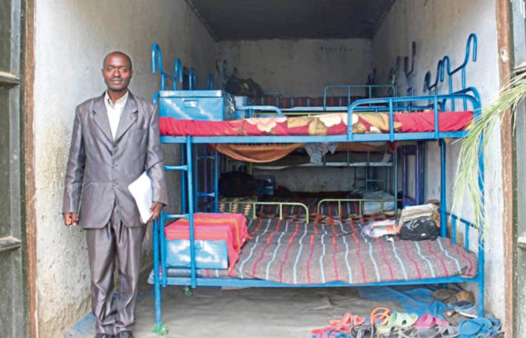 Little Angels School head teacher Kenneth Turyasingura beside the children's current sleeping facilities